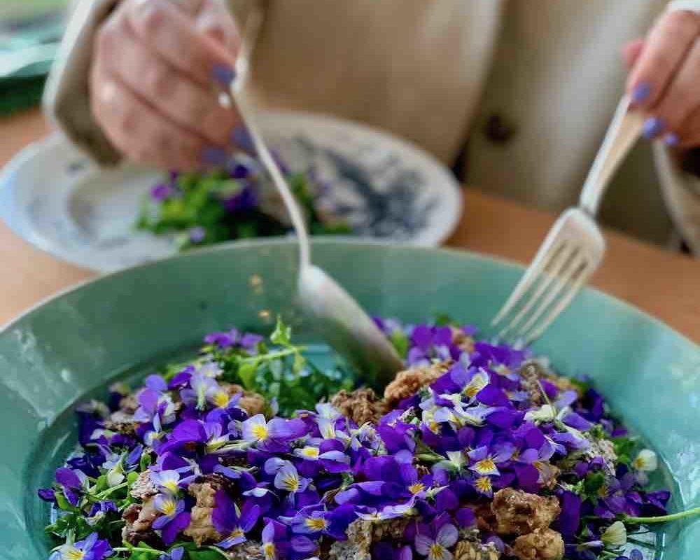 Salat med ville vekster fra skogen, frøknekk, konfitert fett og fioler.