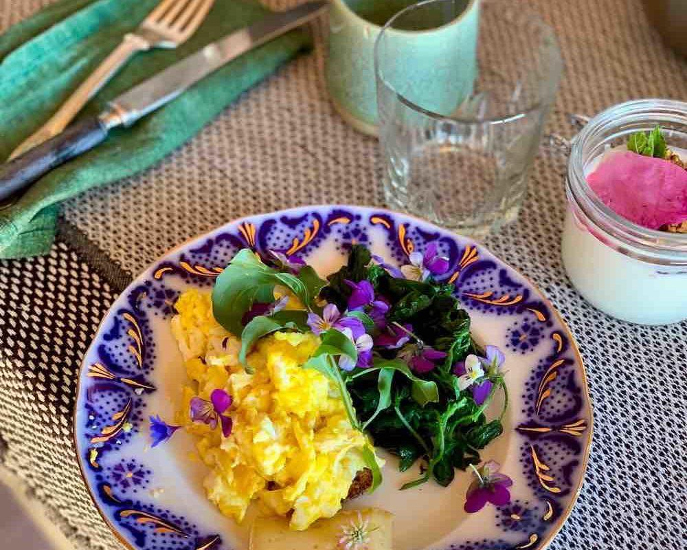 Frokost med grovbrød, lokal ost, egg laget på bålpanne og yoghurt med müsli.